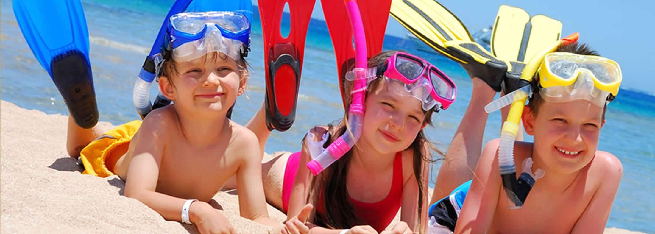 Bambini felici in riva al mare con maschera